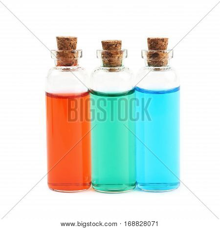 Composition of a few tiny glass vial bottles filled with the colored liquids, composition isolated over the white background