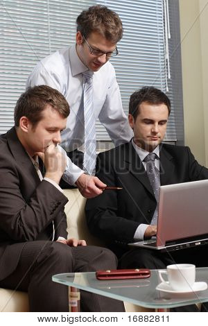 Three business men working together on laptop in the office. one is standing two are sitting on leather sofa