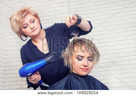 hairdresser blow drying woman's hair after giving a new haircut. Portrait of woman at the hair salon. Hairdresser middle-aged woman making hot styling with use hair dryer. Dynamic shot