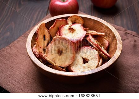 Fruit healthy snack dehydrated apples chips in wooden bowl close up view