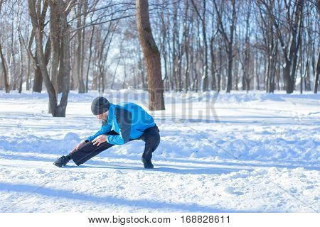 Athletic runner stretching his legs after running workout. Young fitness man stretching leg muscles outdoors in winter park. Fitness concept . Man doing stretching exercise