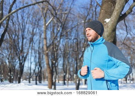 Young man running at winter in park. Athlete man running sport. Runner in winter jogging outdoors. Fitness and healthy lifestyle concept. Winter activities