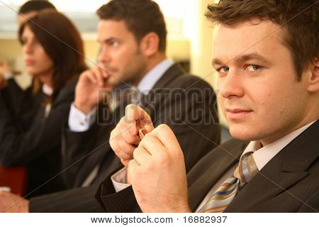 Group of business persons in suits sitting at a conference table, taking part in a meeting and/or presentation - one man in focus, portrait