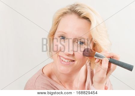 Blonde Lady Smiling And Applying Blush