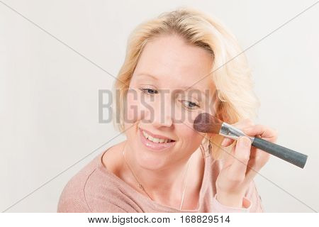 Blonde Lady Smiling And Applying Make-up