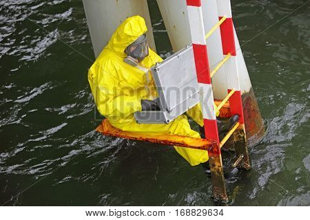 specialist in protective suit and mask with silver case at  ladder above water