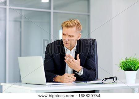 The concept of failure, defeat, crisis the business. A blond frustrated man sits in front of  laptop at his desk in the office.