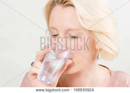 Woman Drinking Water From A Plastic Cup