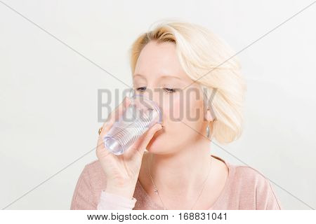 Blonde Woman Over White Background Drinking Water From Plastic C