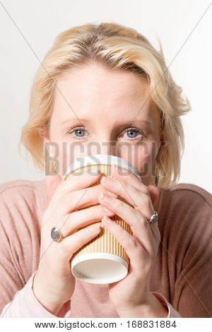 Blonde Woman Directly Gazing While Drinking From A Paper Cup