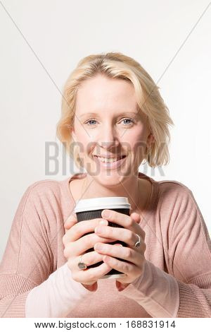Blonde Woman Gazes Directly While Holding A Paper Cup
