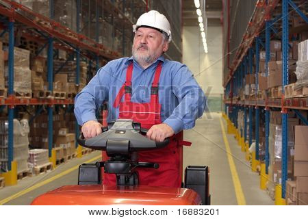 A senior worker driving the fork lift through a storage room in a factory
