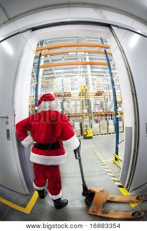 Santa Claus with empty hand powered pallet jack at the gate to gift distribution center