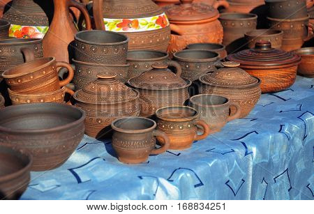 Traditional Ceramic Jugs on Decorative Towel. Showcase of Handmade Ceramic Pottery in a Roadside Market with Ceramic Pots and Clay Plates Outdoors.