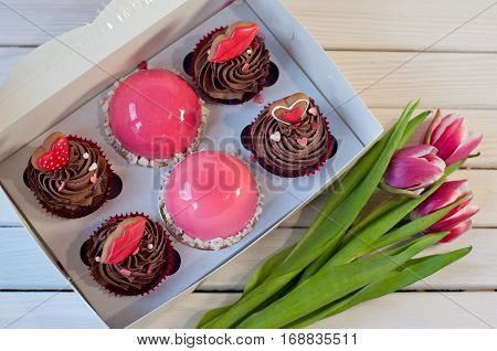Box with brown cupcakes and mousse in rose glaze honey cakes lay on white wooden table near three tulips