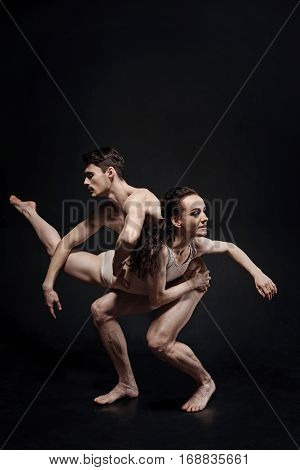 In interaction with my dance partner. Graceful skillful young gymnasts performing in the studio together and expressing elegance while demonstrating their interaction against black background