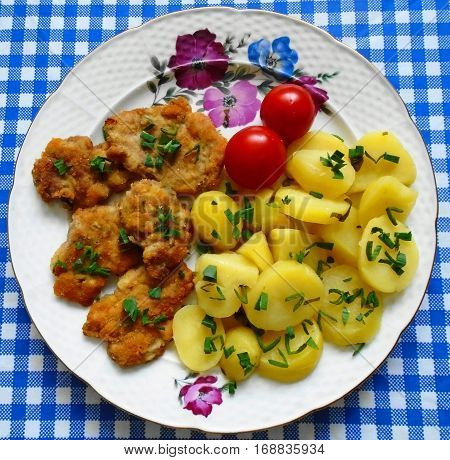 Small schnitzels with potatoes, tomatoes and pieces of lovage levisticum on blue-white tablecloth