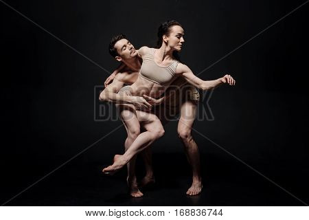 Dance couple in motion. Charismatic skilled young performing against black background and expressing elegance while demonstrating their skills