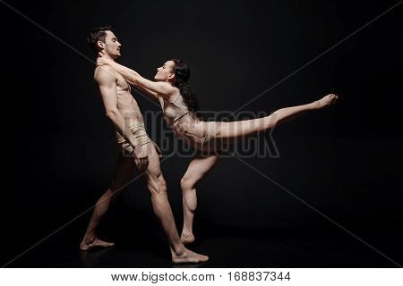 Dancing with my love. Positive artistic flexible performers acting in the studio and dancing while taking part in the art performance isolated in black background