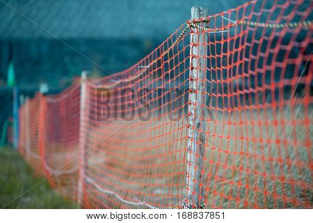 Close-up detail of a wooden fencepost with orange polymer fence mesh netting. Immigration and border control concept.