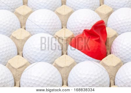 White golf balls in the box for eggs. Golf ball with funny cap.Funny golf concept.