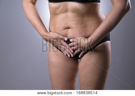 Woman with menstrual pain endometriosis or cystitis stomach ache on gray background