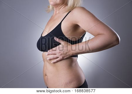 Breast test woman examining her breasts for cancer heart attack pain in human body on gray background