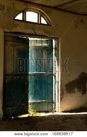 Old blue door is ajar and through the slit pouring sunlight.