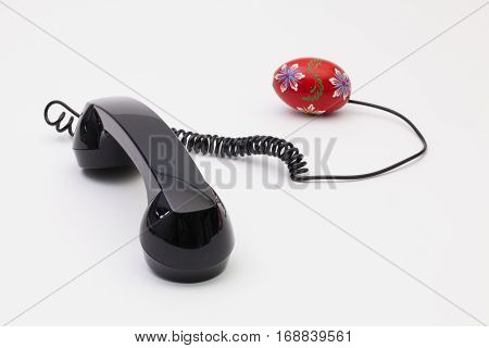 Old phone reciever and cord connection with Easter eggs. Easter hotline concept.