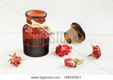 Apothecary dark glass bottle of essential oil, dried rosebuds, white table. Home Aromatherapy.