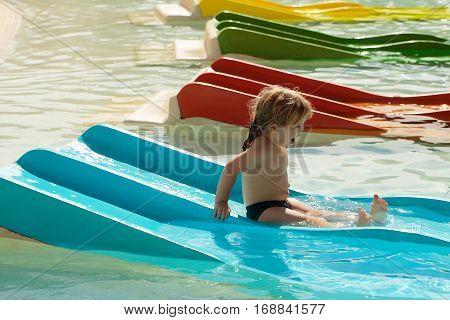 Happy Cute Baby Boy Slides From Blue Waterslide