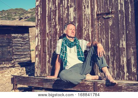 Dreaming Man Traveler Sits On The Porch Of An Old Wooden Hut