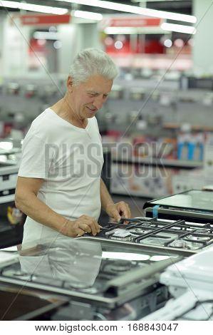 mature man on shopping choosing cooking stove