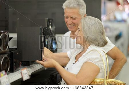 mature couple on shopping, choosing audio system