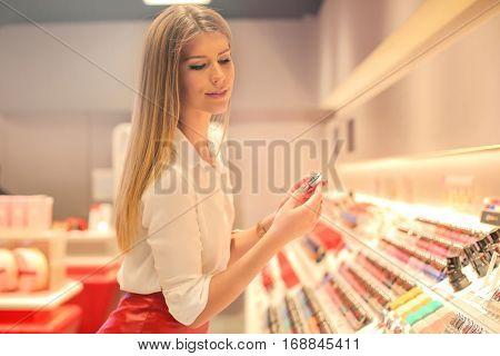 Pretty woman picking nail polish colour in shop