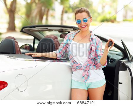 Young woman standing near a convertible with keys in hand - concept of buying a used car or a rental car