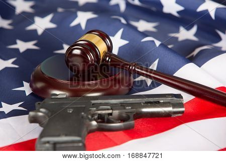 Judge gavel with the United States flag and a pistol