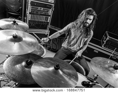 Photo of a male drummer playing his drum set during a concert.
