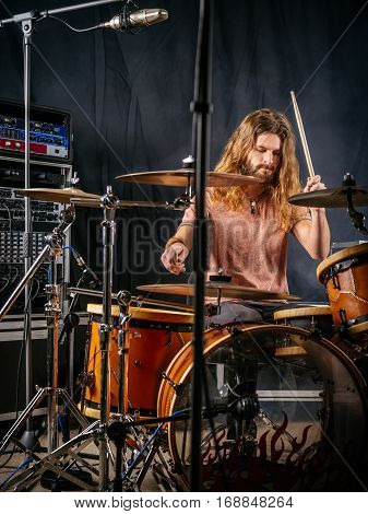 Photo of a male drummer playing his drum set at a recording studio.