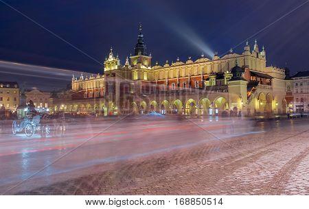 Main Market Square - Rynek Glowny - with Sukiennice - Cloth Hall - with trails of street traffic at night Poland Krakow