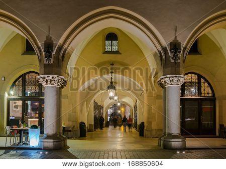 Gothic arcades of Cloth Hall - Sukiennice - on Main Market Square - Rynek Glowny - in Krakow with street restaurant by night