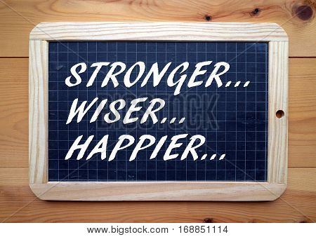 The words Stronger, Wiser, Happier in white text on a blackboard as a reminder of our aspirations for a better, less stressful life