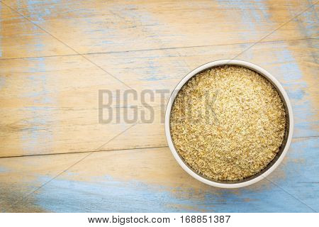 golden flaxseed meal - a ceramic bowl on grunge wood background with a copy space