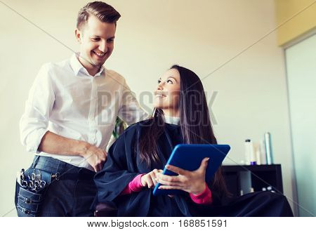 beauty, hairstyle, technology and people concept - happy young woman and stylist with tablet pc computer at salon