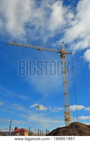 Yellow Crane Building New House on the Construction Site