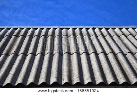 Blue sky over the dangerous asbestos old roof tiles able to use as background.