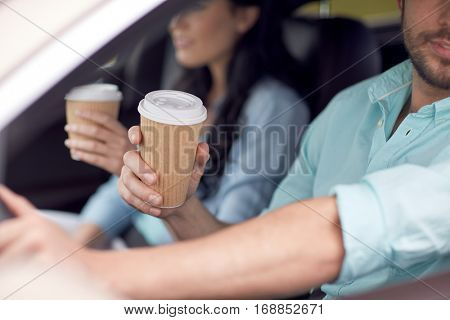 travel, road trip, drinks and people concept - close up of couple driving in car with coffee cups