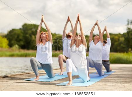 fitness, sport, yoga and healthy lifestyle concept - group of people making low lunge or crescent pose on river berth