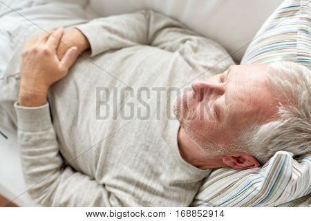 old age, rest, comfort and people concept - close up of senior man sleeping on sofa
