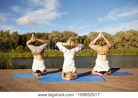 fitness, sport, yoga and healthy lifestyle concept - people making headstand pose on mat on river or lake berth